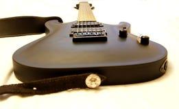 Guitarra eléctrica negra aislada en el fondo blanco Imagenes de archivo