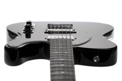 Guitarra eléctrica negra en un fondo blanco Imágenes de archivo libres de regalías
