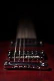 Guitarra eléctrica roja del elemento en un fondo negro Imagen de archivo libre de regalías