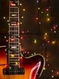 Guitarra eléctrica vieja con una guirnalda encendida en un fondo oscuro Saludo, la Navidad, tarjeta de felicitación del Año Nuevo Imagen de archivo libre de regalías