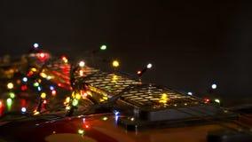 Guitarra eléctrica vieja con una guirnalda encendida en un fondo oscuro Saludo, la Navidad, tarjeta de felicitación del Año Nuevo Foto de archivo