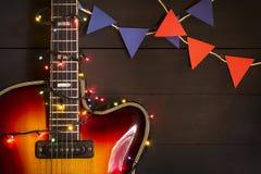 Guitarra eléctrica vieja con una guirnalda encendida en un fondo oscuro Saludo, la Navidad, tarjeta de felicitación del Año Nuevo Imagenes de archivo