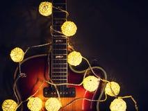 Guitarra eléctrica vieja con una guirnalda encendida en un fondo oscuro Saludo, la Navidad, tarjeta de felicitación del Año Nuevo Imágenes de archivo libres de regalías