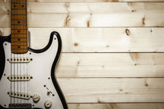 Guitarra eléctrica vieja en el fondo de madera Imagen de archivo libre de regalías