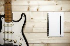 Guitarra eléctrica vieja en el fondo de madera Imágenes de archivo libres de regalías