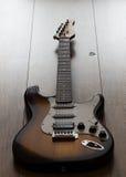 Guitarra elétrica no assoalho de madeira, plectro Imagens de Stock