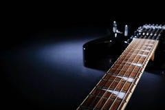 Guitarra elétrica preta moderna Close-up do fingerboard sob o feixe de luz Com espa?o para o texto fotografia de stock royalty free