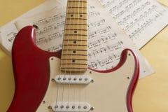 Guitarra elétrica que encontra-se em um fundo colorido e iluminada pela luz natural imagens de stock