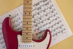 Guitarra el?trica que encontra-se em um fundo colorido e iluminada pela luz natural fotografia de stock