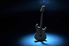 Guitarra em uma fase escura com projetor Fotos de Stock