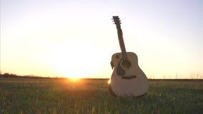 Guitarra en campo en la puesta del sol almacen de video