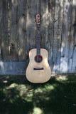Guitarra en la cortina contra una cerca Imagen de archivo libre de regalías