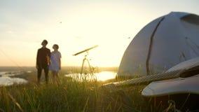 Guitarra en la hierba delante de pares jovenes que disfruta de vacaciones de verano al aire libre en la puesta del sol metrajes