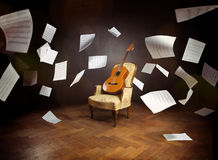 Guitarra en una silla vieja con las hojas de música del vuelo Foto de archivo
