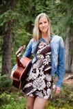 Guitarra fêmea da terra arrendada de encontro às árvores Imagens de Stock Royalty Free