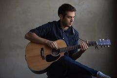 Guitarra practicante del talento joven foto de archivo