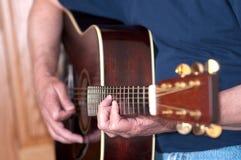 Guitarra que es jugada por el músico de sexo masculino Imagen de archivo
