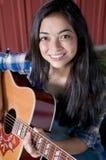 Guitarra que juega adolescente por el granero Imagen de archivo libre de regalías