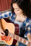 Guitarra que juega adolescente por el granero Imagenes de archivo