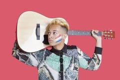 Guitarra que lleva del adolescente con la bandera holandesa en su cara sobre fondo rosado Fotografía de archivo libre de regalías