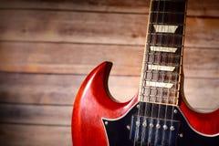 Guitarra roja del vintage con el fondo de madera del panel Fotografía de archivo