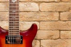 Guitarra roja y pared de ladrillo gruesa fotografía de archivo