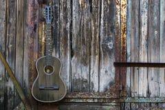 Guitarra velha na parede de madeira Imagens de Stock Royalty Free