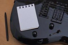 Guitarra y cuaderno imagen de archivo