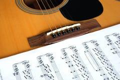 Guitarra y notas musicales Foto de archivo