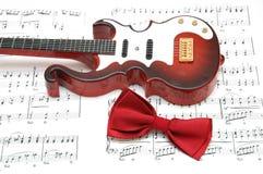 Guitarra y pajarita sobre la hoja de la música impresa Fotos de archivo libres de regalías
