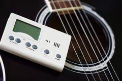 Guitarra y sintonizador para los instrumentos musicales Imágenes de archivo libres de regalías