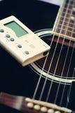 Guitarra y sintonizador para los instrumentos musicales Fotografía de archivo libre de regalías