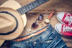 Guitarra, zapatillas de deporte, gafas de sol, sombreros, relojes, accesorios de la ropa para los hombres en el piso de madera Imagenes de archivo