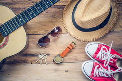 Guitarra, zapatillas de deporte, gafas de sol, sombreros, relojes, accesorios de la ropa para los hombres en el piso de madera Foto de archivo