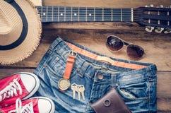 Guitarra, zapatillas de deporte, gafas de sol, sombreros, relojes, accesorios de la ropa para los hombres en el piso de madera Fotos de archivo
