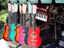 Guitarras coloridas en departamento de los instrumentos musicales Foto de archivo libre de regalías