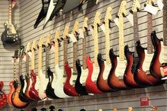 Guitarras para la venta en la pared imagen de archivo libre de regalías