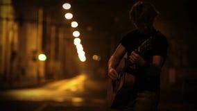 Guitarrista adolescente que juega en la calle de la noche con efecto unfocusing almacen de video