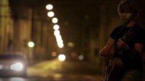 Guitarrista adolescente que juega en la calle de la noche mientras que los coches lo pasan cerca metrajes