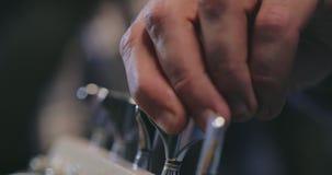 Guitarrista baixo que verifica como as cordas baixas são ajustadas video estoque