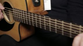 Guitarrista com guitarra acústica O guitarrista joga uma guitarra da guitarra da seis-corda video estoque