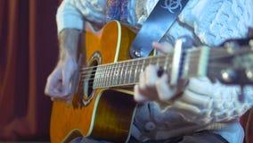 Guitarrista de la guitarra acústica que juega acordes Instrumento musical con las manos del ejecutante metrajes