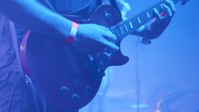 Guitarrista de la roca delante de una muchedumbre en un acontecimiento de la música almacen de metraje de vídeo