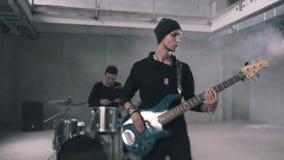 Guitarrista del batería y del bajo que toca los instrumentos en un cuarto ahumado Banda de rock plan medio almacen de video