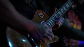 Guitarrista do ator que joga a guitarra O músico joga um instrumento musical no solo da fase vídeos de arquivo