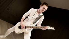Guitarrista elegante del ritmo con diversos ojos en la ropa blanca en un fondo negro que juega expresivo el blanco almacen de video