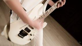 Guitarrista elegante del ritmo con diversos ojos en la ropa blanca en un fondo negro que juega expresivo el blanco almacen de metraje de vídeo