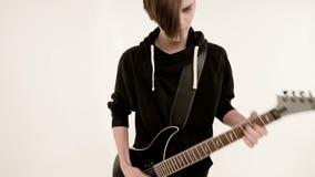 Guitarrista elegante del ritmo con diversos ojos en ropa negra en un fondo blanco que juega expresivo el negro almacen de video