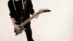 Guitarrista elegante del ritmo con diversos ojos en ropa negra en un fondo blanco que juega expresivo el negro metrajes