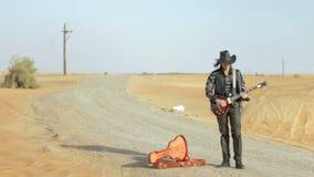 Guitarrista en el camino del desierto almacen de metraje de vídeo